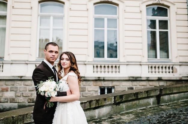 Jonggehuwden staan in de buurt van oude architectuur, gebouw, oud huis buiten, vintage paleis buiten. romantische liefde in vintage sfeerstraat.