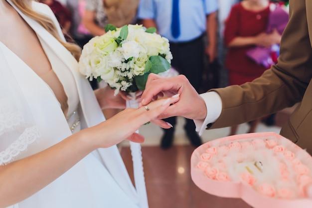 Jonggehuwden voegen handtekeningen toe in een registratiekantoor tijdens huwelijksregistratie.