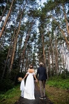 Jonggehuwden wandelen langs een pad in het bos