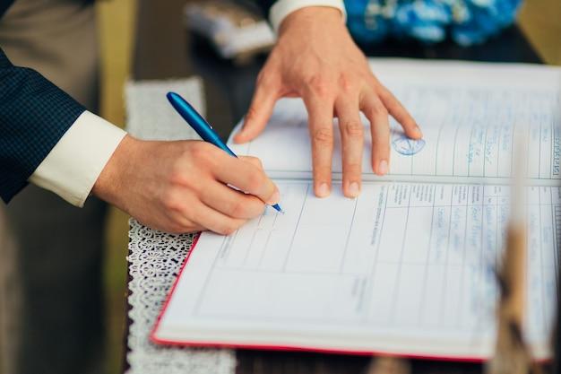 Jonggehuwden zetten hun handtekening bij het registreren van een huwelijk