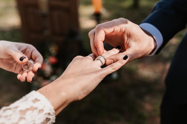 Jonggehuwden zetten ringen op, ruilen ringen, trouwringen, huwelijksceremonie, stel, jong stel, liefde, ringen.