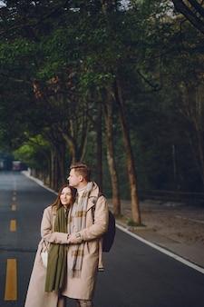 Jonggehuwdepaar die affectie tonen en handen houden aangezien zij door het nationale bospark van zhangjiajie lopen