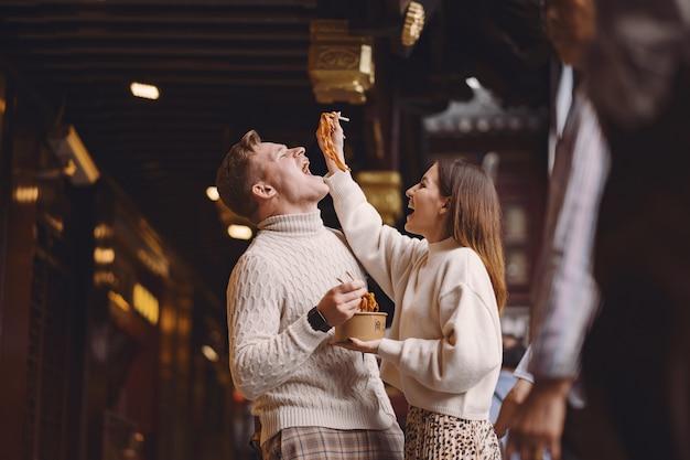 Jonggehuwdepaar die noedels met eetstokjes in shanghai buiten een voedselmarkt eten