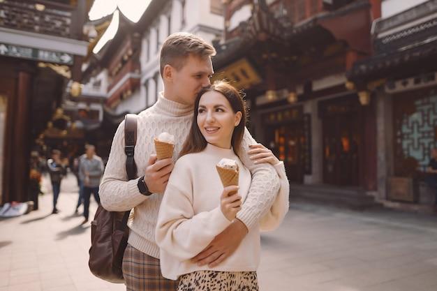 Jonggehuwdepaar die roomijs van een kegel op een straat in shanghai dichtbij yuyuan china eten.
