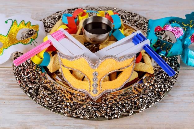 Joods carnaval purim-feest op hamantaschen-koekjes, lawaaimaker en masker met perkament