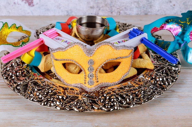 Joods carnaval purim-feest op hamantaschen-koekjes, lawaaimaker en masker
