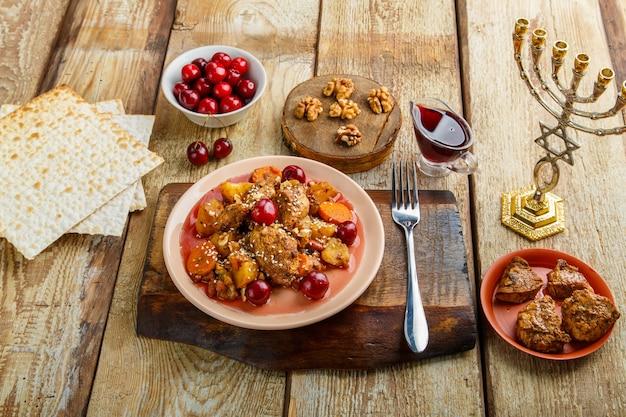 Joods gerecht gestoofde aardappelen met kip in kersensaus, versierd met kersen op een standaard naast matze en menora. horizontale foto