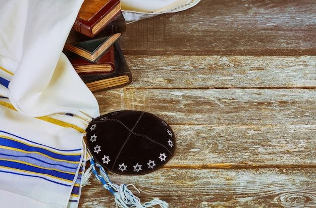 Joods ritueel met keppel in talit bidden in het joodse hebreeuwse gebedenboek over een synagoge