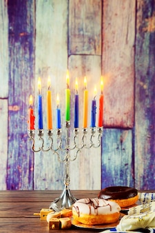 Joods symbool joodse feestdag hanukkah met menora traditionele kandelaar en houten dreidels spinni...