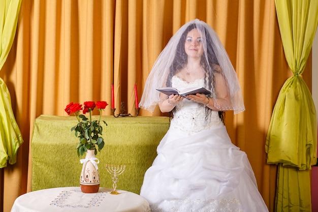 Joodse bruid in een witte jurk, gesluierd gezicht aan een tafel met bloemen, leest een gebed voor voor de hupa-ceremonie