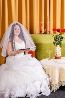 Joodse bruid in witte jurk met gesluierd gezicht zit tegilim te lezen voor de chupa-ceremonie