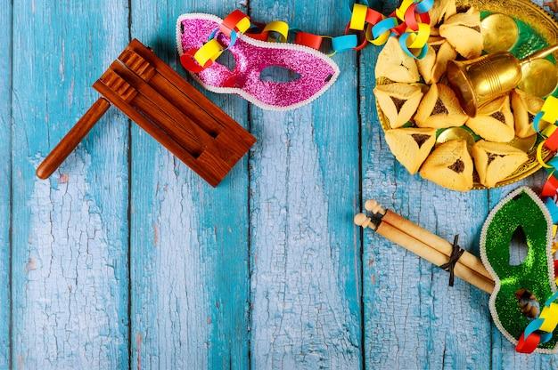 Joodse carnaval purim-viering op hamantaschenkoekjes, noisemaker en masker met perkament