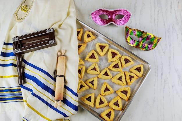 Joodse driehoekskoekjes voor purim met talliet, tora en lawaaimaker.