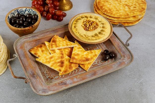 Joodse eettafel met pitabroodje, hummus en olijven.