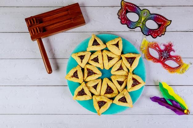Joodse koekjes haman oren voor purim met masker en lawaaimaker.