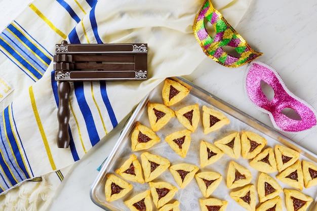 Joodse koekjes haman-oren voor purim met masker, talliet en lawaaimaker.