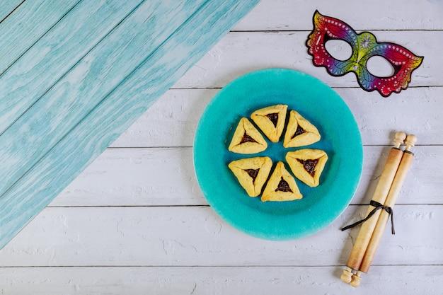 Joodse koekjes haman oren voor purim met tora papyrusrol en masker.