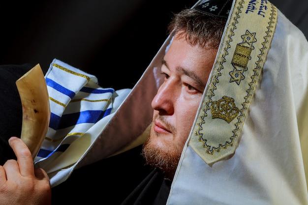 Joodse man blaast de shofar-hoorn van rosh hashanah nieuwjaar