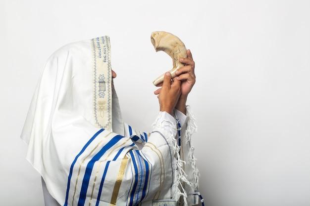 Joodse man in tallit die de sjofar van rosj hasjana (nieuwjaar) blaast. religieus symbool. blazen op de sjofar voor het trompettenfeest, jood in een traditionele tallit gebedssjaal die op de ramshoorn blaast