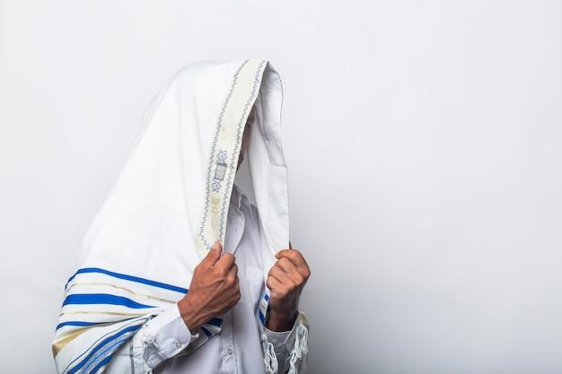 Joodse man in verpakt tallit gebed religieuze orthodoxe met bidt in jeruzalem, israël. een rabbijn die 's ochtends een gebedssjaal draagt. witte gebedssjaal - talliet, joods religieus symbool.