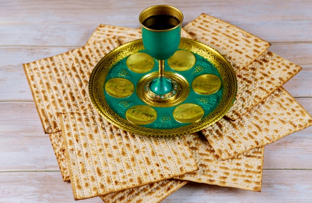 Joodse matzah, kiddush en seder met tekst in hebreeuws ei, bot, kruiden, karpas, chazeret en charoset. pascha concept.
