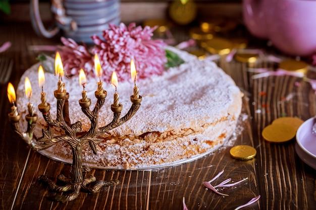 Joodse menora met kaarsen en vakantie taart versierd met bloemen