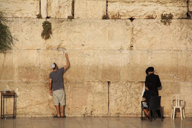 Joodse mensen bidden tot de westelijke muur van jeruzalem