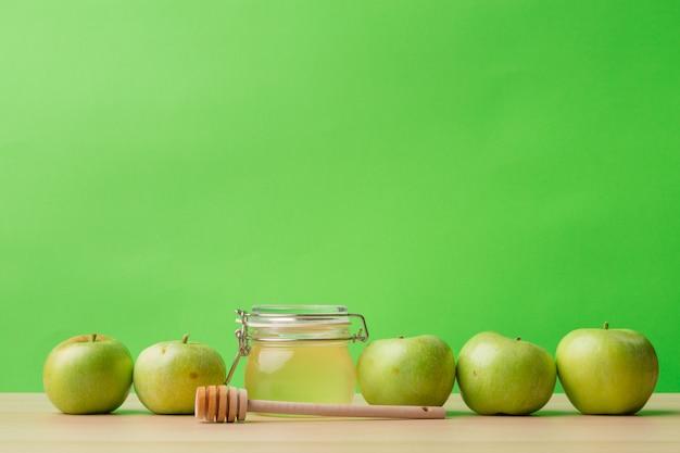 Joodse vakantie rosh hashanah achtergrond met honing en appels op houten tafel. copsyspace