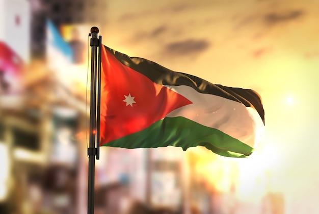 Jordanië vlag tegen stad wazige achtergrond bij zonsopgang achtergrondverlichting