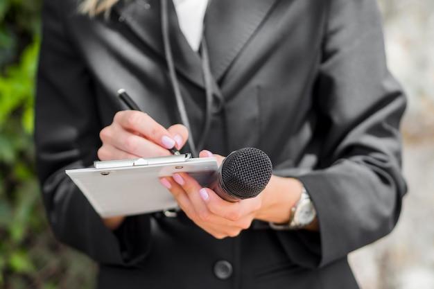 Journalist die zwart kleren middelgroot schot draagt
