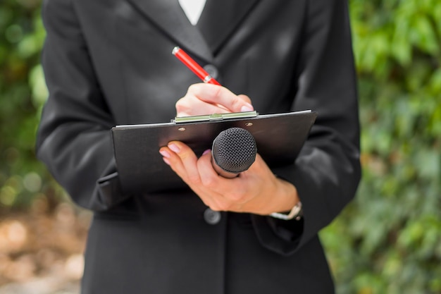 Journalist die zwarte kleren draagt die microfoon houden