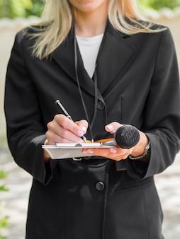 Journalist draagt zwarte kleding schrijft