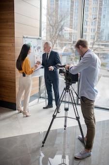 Journalisten en hun gasten zoeken het druk in de studio tijdens het maken van een video