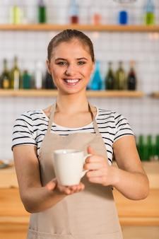Jouw bestelling. positieve aardige jonge barista die lacht en naar je kijkt terwijl je een kopje koffie drinkt