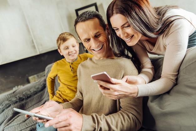 Jouw mening. vrolijke jonge vrouw die op de rug van de bank leunt en haar echtgenoot de foto's op haar telefoon toont terwijl de man lacht