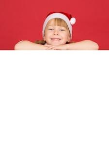 Jouw tekst hier. verticale studio shot van een klein meisje glimlachend liggend op de top van het witte lege bordje met copyspace