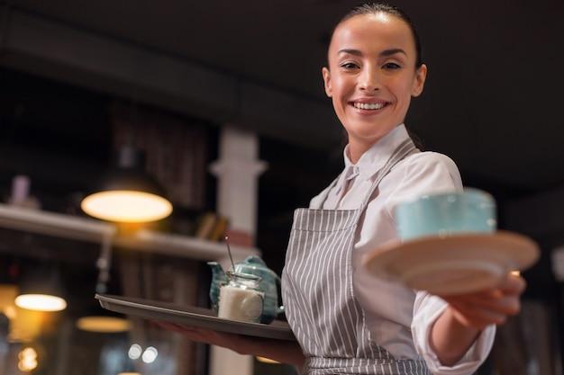 Jouw thee. blije aantrekkelijke mooie serveerster die thee serveert terwijl ze het dienblad vasthoudt en grijnzend