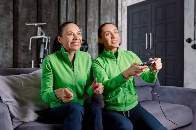 Joystick van gameconsole in handen van vrouw die speelt met steun van haar zus