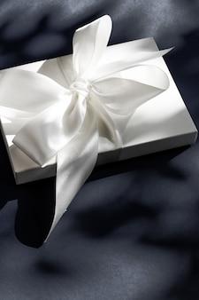 Jubileumviering winkelverkooppromotie en luxe verrassingsconcept luxe vakantie witte geschenkdoos met zijden lint en strik op zwarte achtergrond luxe bruiloft of verjaardagscadeau