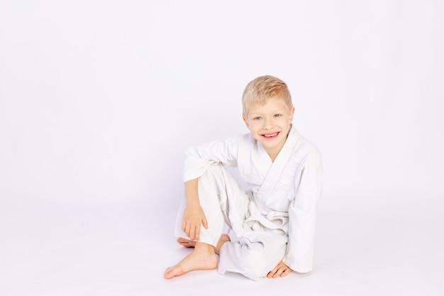 Judo en sportconcept, blonde jongenszitting in judogi
