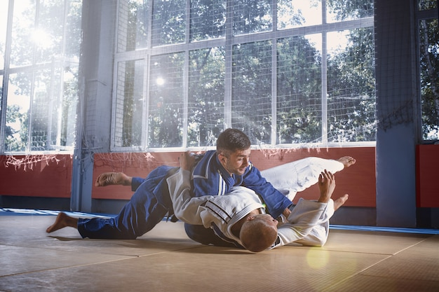 Judo-jagers die technische vaardigheden tonen tijdens het beoefenen van vechtsporten in een vechtclub