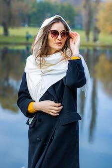 Juffrouw gekleed in jas met bril bij het meer