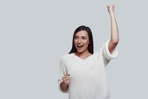 Juichen. aantrekkelijke jonge vrouw die wegkijkt en glimlacht terwijl ze tegen een grijze achtergrond staat