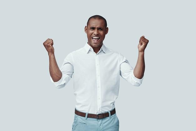 Juichen. knappe jonge afrikaanse man gebaren en glimlachen terwijl hij tegen een grijze achtergrond staat