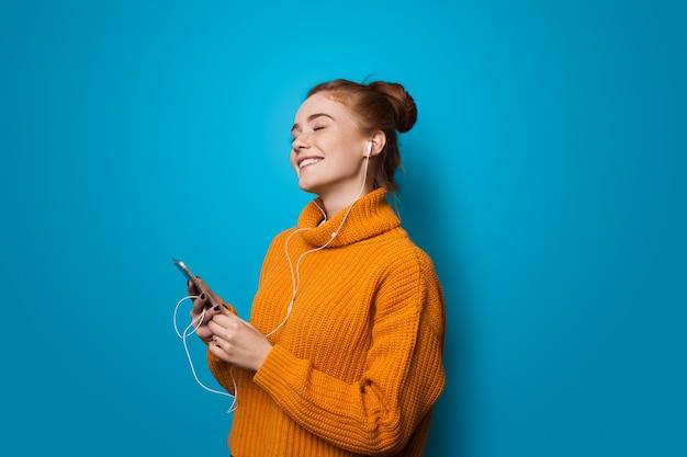 Juichende blanke dame met sproeten en rood haar lachend tijdens het luisteren naar muziek op een blauwe muur
