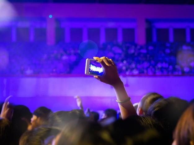 Juichende fans nemen een foto of video met smartphone in een gratis live concert