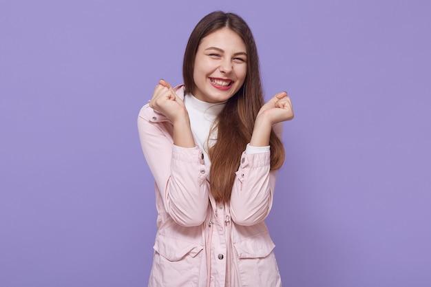Juichende gelukkige jonge blanke vrouw met mooie uitstraling balde vuisten, ziet er opgewonden en vreugdevol uit, vrouw schreeuwt van geluk om haar doelen te bereiken.