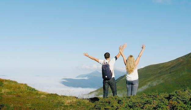 Juichende vieren gelukkige mensen op wandeling opgewonden met armen opgewekt in leuke vrolijke viering bij zonsondergang