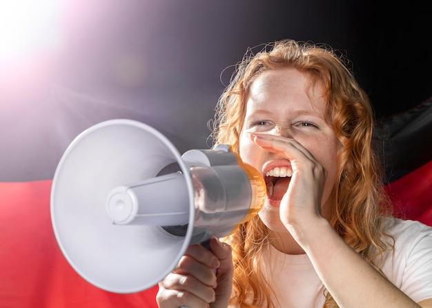 Juichende vrouw die in megafoon met duitse vlag spreekt
