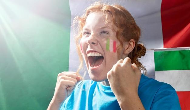 Juichende vrouw met de italiaanse vlag op zijn gezicht